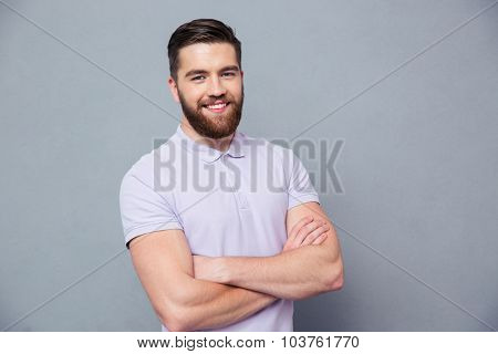 Portrait of a happy casual man standing with arms folded over gray background and looking at camera