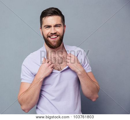 Portrait of a smiling hipster man looking at camera over gray background