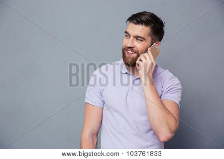 Portrait of a happy casual man talking on the phone over gray background
