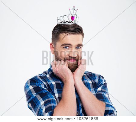 Portrait of a happy feminine man in queen crown standing isolated on a white background and looking at camera
