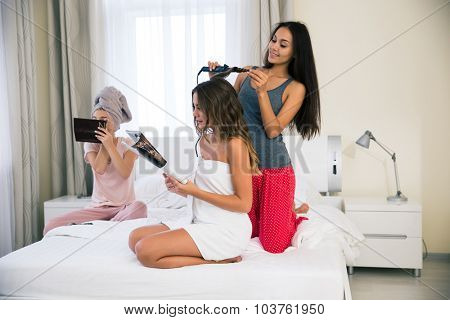 Portrait of a three girls doing makeup and hairstyle at home