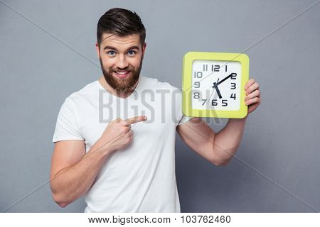 Portrait of a happy casual man pointing finger on wall clock over gray background