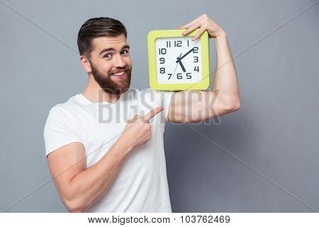 Portrait of a smiling casual man pointing finger on wall clock over gray background