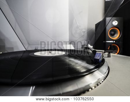 Close up view of old fashioned turntable playing a track from black vinyl