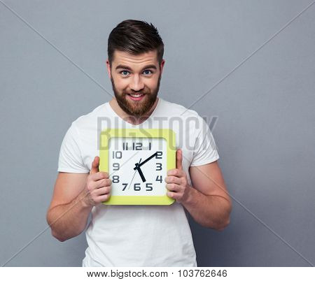 Portrait of a happy man holding wall clock over gray background and looking at camera