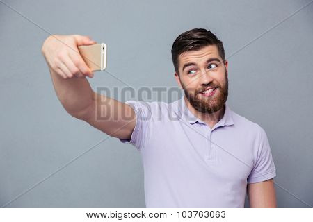 Portrait of a happy man making selfie photo on smartphone over gray background