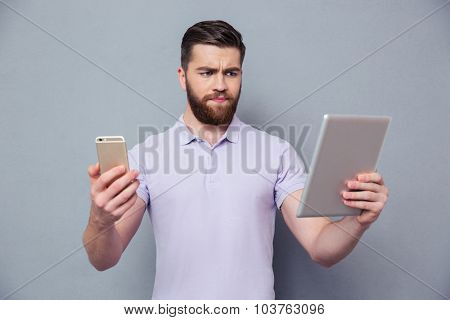 Portrait of a young man choosing between tablet computer and smartphone over gray background