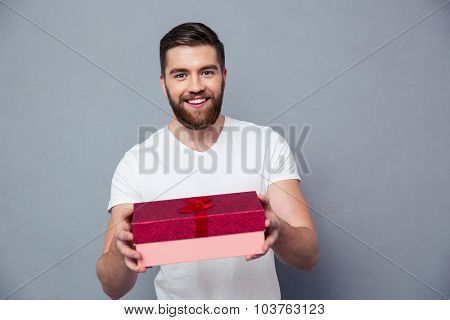 Portrait of a happy man giving gift box on camera over gray background