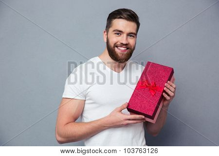 Portrait of a smiling casual man holding gift box over gray background and looking at camera