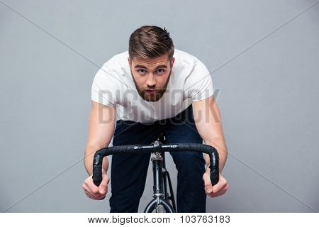 Portrait of a handsome man riding on the bicycle over gray background