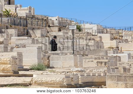 JERUSALEM, ISRAEL - JULY 13, 2014: Man prays on Jewish cemetery on Mount of Olives - most ancient and important cemetery where burials started 3,000 years ago with about 70,000 tombs. (Focus on man).