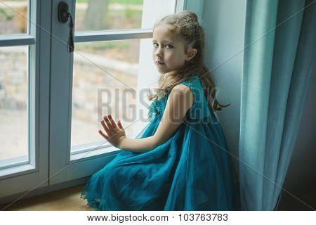 Sad girl looking through window