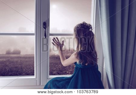 Sad girl looking through window