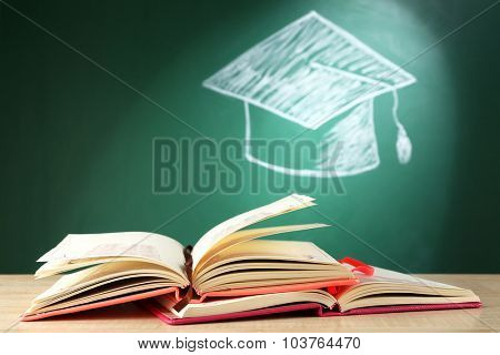 Open books and bachelor hat drawing on blackboard background