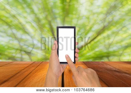 Male Hand Is Holding A Modern Touch Screen Phone And Blur Image Of Abstract Bokeh Of Tree