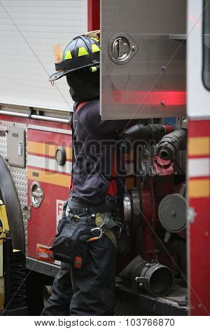 Fire fighter stowing gear into truck