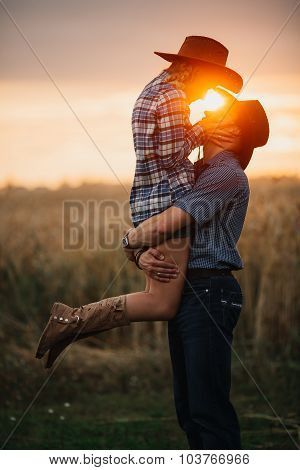 Couple of young adults in love by  at sunset. Man holding a woman his arms.