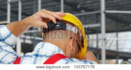 Head of Construction worker with helmet  over industrial background.