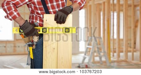 Handyman with wood plank and level on construction background.