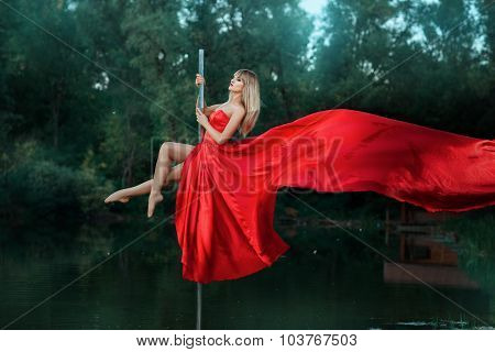 Girl Dancing On A Pole And Her Dress Develops.