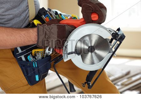 Construction Worker hands with circular saw over house background.