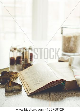 Opened cookbook with cookie cutters and kitchen storage bottles on background, selective focus. Text in a book is not recognizable.