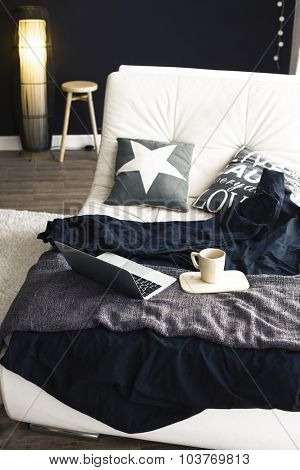 Cozy couch with blanket, coffee and laptop in modern interior in black and white colors