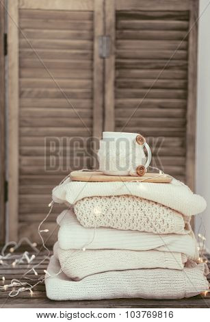 Knitwear closeup, stack of white sweaters on old rustic background, pastel colors.