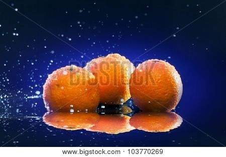 ripe oranges lying on mirror in sprays of water and water drops on dark blue background