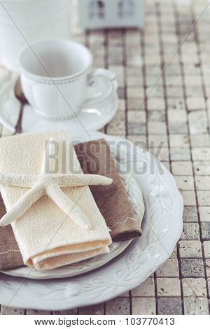 Beach style table setting with starfish decor on mosaic stone background