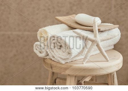 Hotel bathroom decor closeup. White towels, soap, loofah and starfish on wooden stool over stone tile. Natural colors, still life.