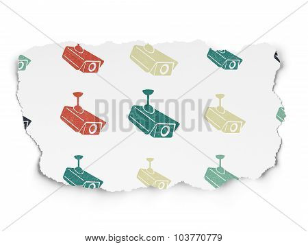 Privacy concept: Cctv Camera icons on Torn Paper background