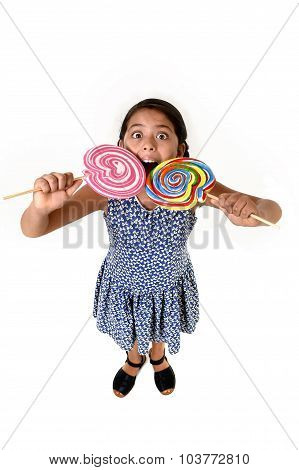 Happy Female Child Wearing Dress Eating Two Huge Lollipop At Once Having Fun In Sugar Addiction