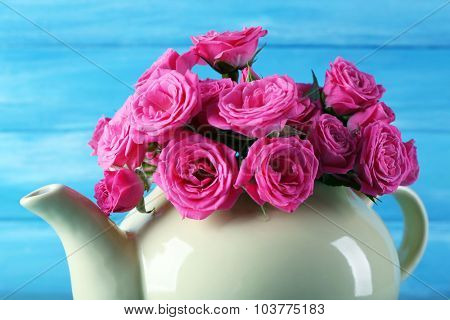 Beautiful roses in teapot on wooden background