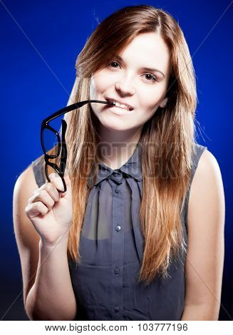 Young Woman Biting A Nerd Glasses With Interested Look