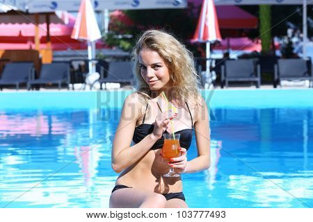 Young woman enjoying cocktail in swimming pool at summertime