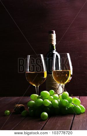 Bottle and glasses of wine with grape on wooden background