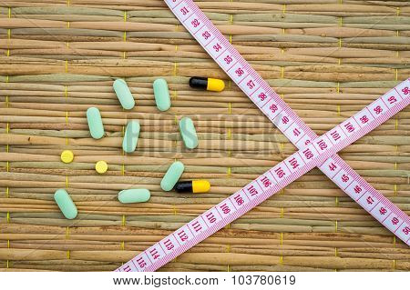 Pills And Cross Measuring Tape On Traditional Mat. Diet Or Lose Weight Concept.