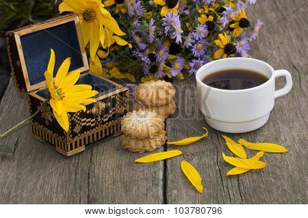 Open Casket, Coffee, Cookies, Petals And Wild Flowers On An Old Table