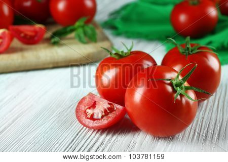 Whole and sliced red tomatoes on wooden table, close-up