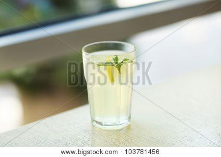 Glass of lemonade on blurred background
