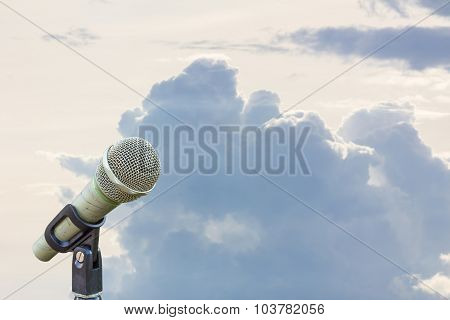 Microphone On A Stand With Blurred Gray Big Cloud Before Raining In The Morning, Copyspace On The Ri