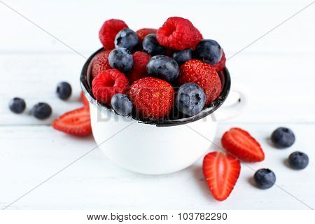 Tasty ripe berries in cup on wooden table close up