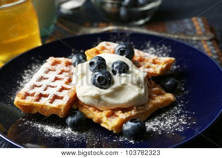 Sweet homemade waffles with blueberries and cream on plate, on dark wooden background