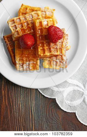 Sweet homemade waffles with strawberries  on plate, on table background