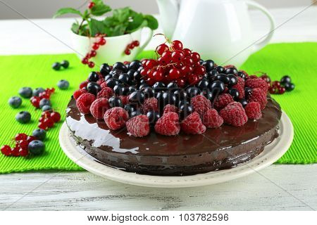 Delicious chocolate cake with summer berries on wooden table with green napkin, closeup
