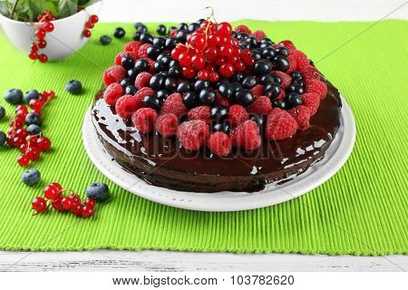 Delicious chocolate cake with summer berries on green tablecloth, closeup