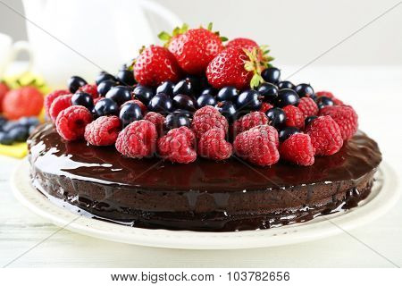 Delicious chocolate cake with summer berries on white wooden table, closeup