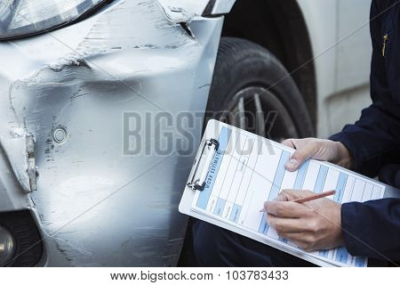 Auto Workshop Mechanic Inspecting Damage To Car And Filling In Repair Estimate