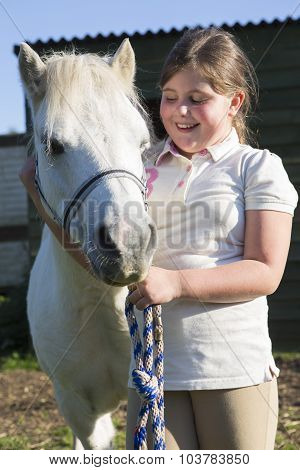 Girl Looking After Pet Pony